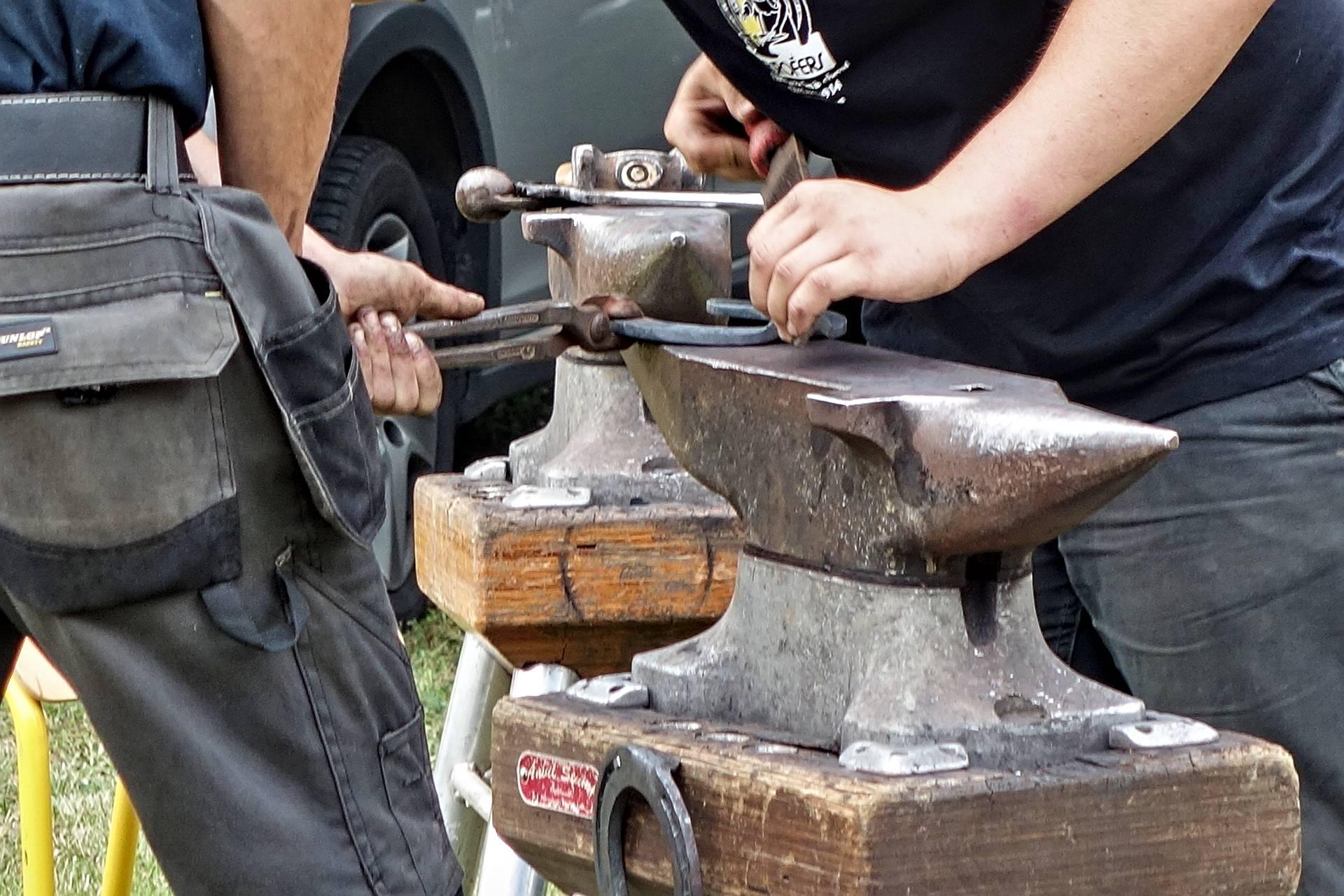 Un epaie de mains s'activant autour d'un fer à cheval posé sur une enclume de forgeron