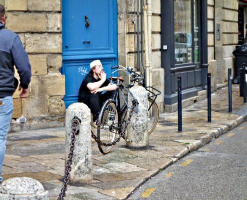 Homme assis devant une porte dans la rue