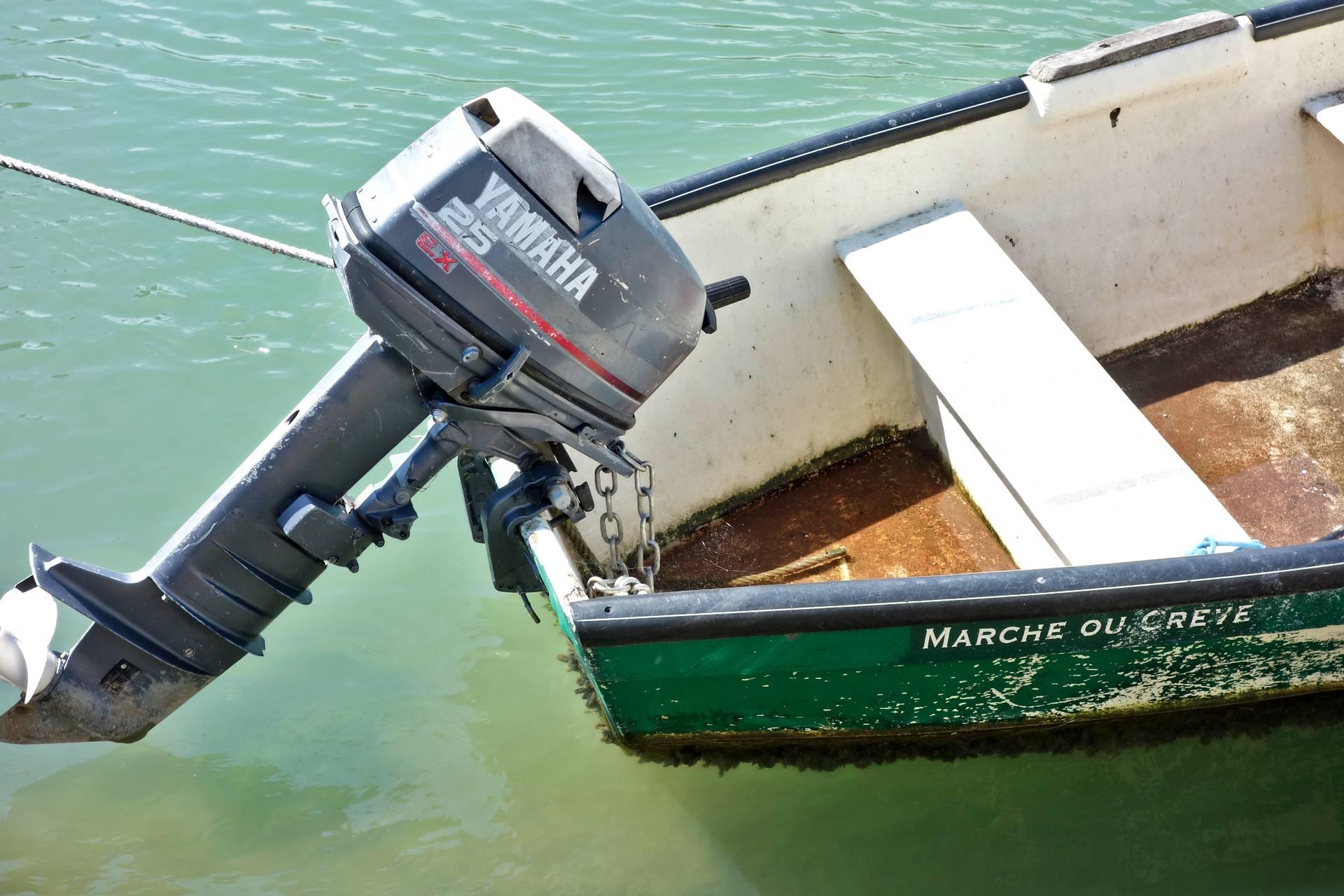 Poupe d'un canot à moteur baptisé «marche ou crève»
