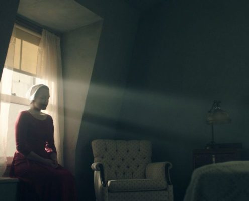 La servante écarlate assise en contre-jour devant la fenêtre de sa chambre