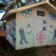 Cabane de maintenance avec fresque décorative représentant des rouages et des ouvriers