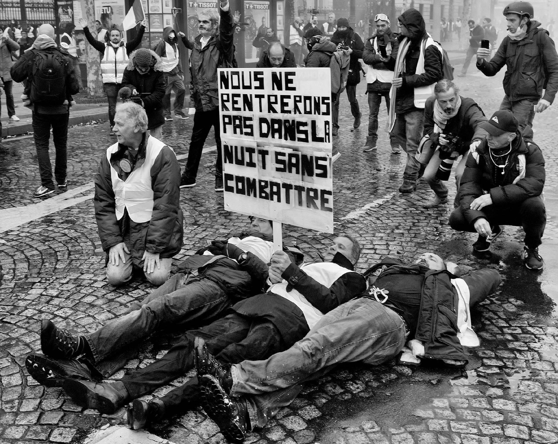 Manifestation du 24novembre 2018 à Paris, des hommes allongés sur la chausséerefusent de partir.