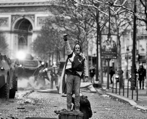 Un manifestant en gilet jaune poing levé avec les pomper et l'Arc de Triomphe au fond