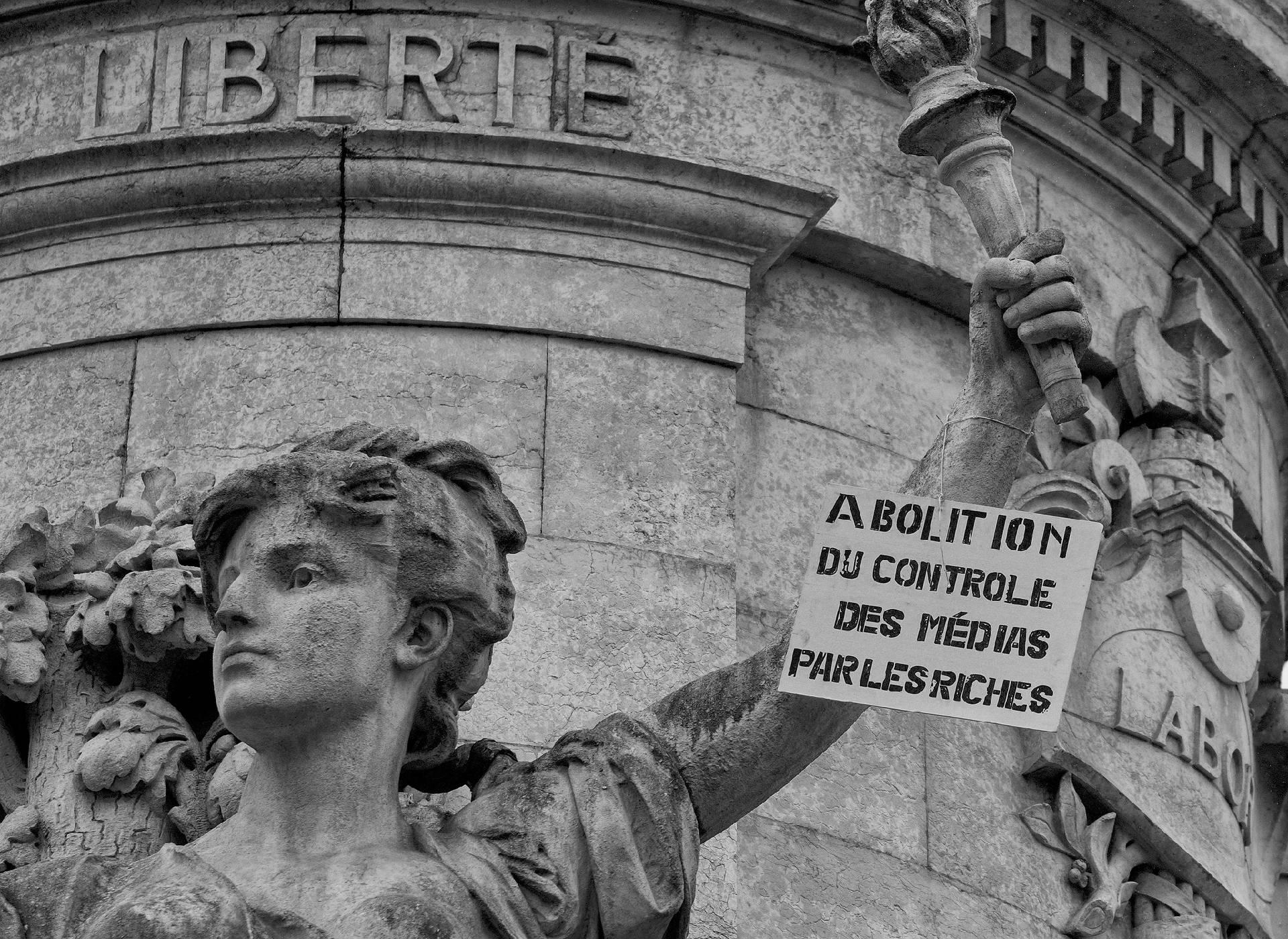 Pancarte réclamant l'abolition du contrôle des médias par les riches