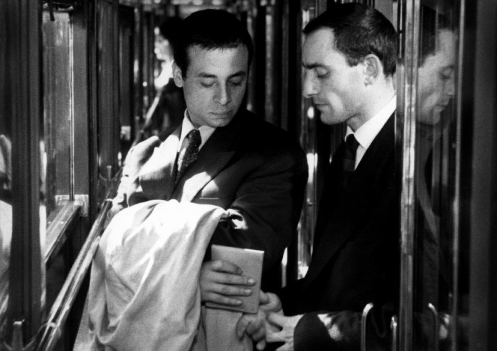 Deux hommes en costume se passent discrètement un portefeuilles dans une allée de train
