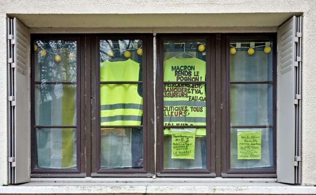 Fenêtre avec gilets jaunes à slogans anti-Macron