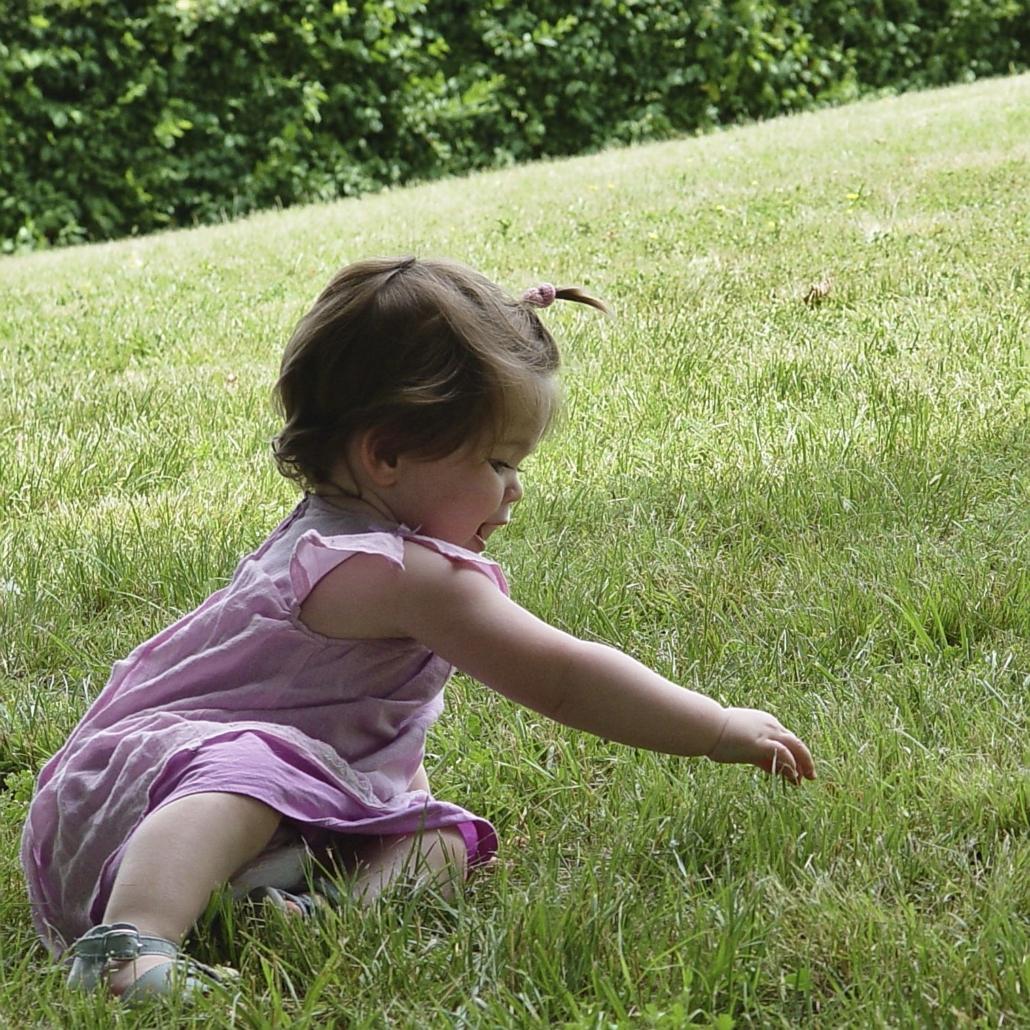 Une toute petite fille habillée en rose qui joue dans l'herbe.